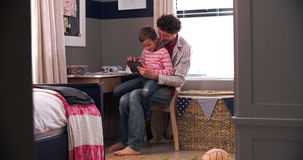 Father And Son Sitting In Bedroom Using Digital Tablet. Boy sitting with father at desk in bedroom using digital tablet.Shot on Sony FS700 at frame rate of 25fps stock footage