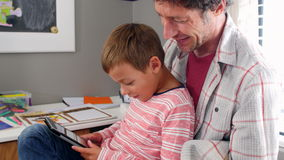 Father And Son Sitting In Bedroom Using Digital Tablet stock footage