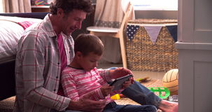 Father And Son Sitting In Bedroom Using Digital Tablet. Boy sitting with father on floor in bedroom using digital tablet.Shot on Sony FS700 at frame rate of stock video