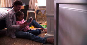 Father And Son Sitting In Bedroom Using Digital Tablet. Boy sitting with father on floor in bedroom using digital tablet.Shot on Sony FS700 at frame rate of stock video footage