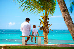 Father and son sitting on bench in front of the ocean Stock Photography