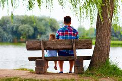 Father and son sitting on the bench near the lake Stock Photo