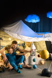 Father and son sitting in blanket fort together and looking away Stock Photography