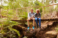 Father and son sitting on a bridge in a forest playing Stock Images