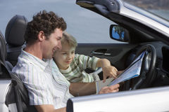 Father and son (6-8) sitting in convertible car, looking at road map, smiling, side view Royalty Free Stock Images