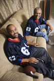 Father and son sitting on couch. Portrait of an African-American father and son sitting on couch smiling and wearing football jerseys Stock Photo