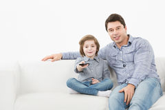 Father and son sitting on the couch with the TV remote control Royalty Free Stock Photos