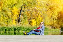 Father and son are sitting on the dock. Autumn, sunny. Side view.  Royalty Free Stock Photography