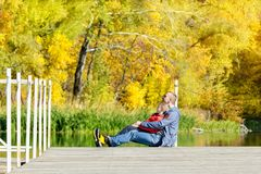 Father and son are sitting on the dock. Autumn, sunny. Side view.  Stock Images