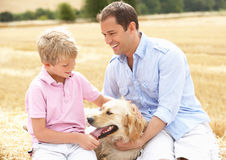 Father And Son Sitting With Dog On Straw Bales In. Harvested Field Smiling Stock Photo
