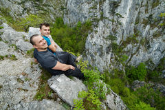Father and son sitting on the edge of a cliff Stock Photos