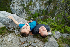 Father and son sitting on the edge of a cliff Royalty Free Stock Photo