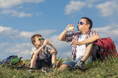 Father and son sitting in the field at the day time. Stock Photography