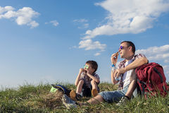 Father and son sitting in the field at the day time. Stock Image