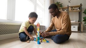 Father and son sitting on floor play with toy blocks royalty free stock photography