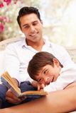 Father And Son Sitting In Garden Reading Book Together Stock Image