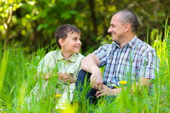 Father and son sitting in grass Stock Photos