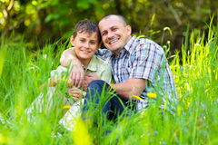 Father and son sitting in grass stock photography