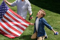 Father and son sitting on grass with us flag, boy screaming and holding soda can Royalty Free Stock Photo