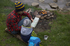Father and son sitting near a campfire at the campsite and are l stock image