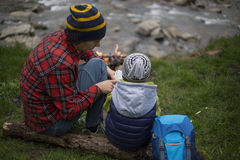 Father and son sitting near a campfire at the campsite and are l stock images