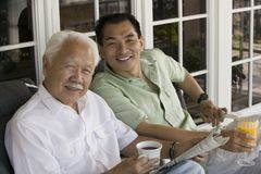 Father and son sitting outside home Stock Images