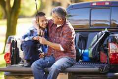 Father And Son Sitting In Pick Up Truck On Camping Holiday. Smiling At Each Other Royalty Free Stock Photos