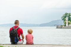 Father and son sitting on the pier on the sea background, lighthouse and mountains in the distance. Back view Stock Image