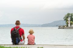 Father and son sitting on the pier on the sea background, lighthouse and mountains in the distance. Back view Royalty Free Stock Image
