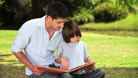 Father and son sitting reading outdoors. Father and his son sitting reading a book on the grass stock footage
