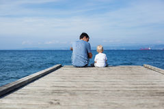 Father with son sitting on the sea pier Stock Photos