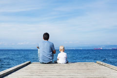 Father with son sitting on the sea pier Stock Photography