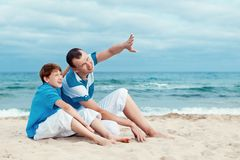 Father and son sitting on sea Stock Images