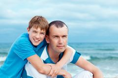 Father and son sitting on sea Royalty Free Stock Photos