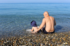 Father and son sitting on the seaside Royalty Free Stock Image