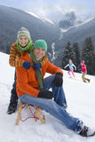 Father and son sitting on sled on ski slope Stock Photo