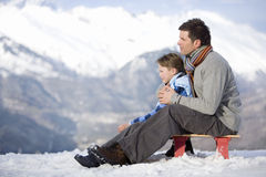 Father and son (7-9) sitting on sled in snow field, side view, mountain range in background Stock Photo