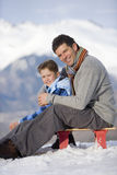 Father and son (7-9) sitting on sled in snow field, smiling, portrait, mountain range in background stock image