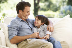 Father And Son Sitting On Sofa At Home stock photos