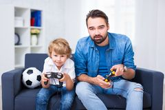 Father and son sitting on sofa at home and playing video game. Fatherhood - father and son sitting on sofa at home and playing video game stock photography