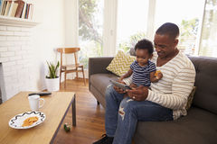 Father And Son Sitting On Sofa At Home Using Digital Tablet Stock Photos