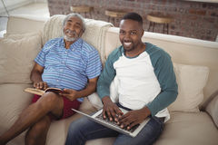 Father and son sitting on sofa with laptop and book in living room. Portrait of smiling father and son sitting on sofa with laptop and book in living room Royalty Free Stock Photography
