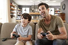 Father And Son Sitting On Sofa In Lounge Playing Video Game Royalty Free Stock Image