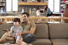 Father And Son Sitting On Sofa In Lounge Watching Television Royalty Free Stock Photos