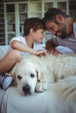 Father and son sitting on sofa with pet dog in living room. At home stock image