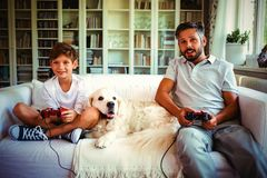 Father and son sitting on sofa with pet dog and playing video games royalty free stock image