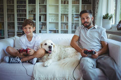 Father and son sitting on sofa with pet dog and playing video games. At home Royalty Free Stock Image