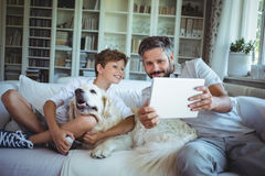 Father and son sitting on sofa with pet dog and using digital tablet Stock Photography
