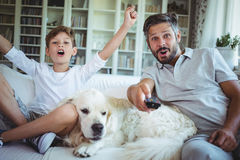 Father and son sitting on sofa with pet dog and watching television. In living room at home Stock Image