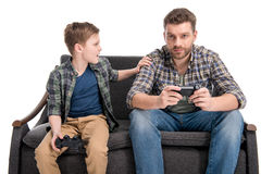 Father and son sitting on sofa and playing with joysticks. Isolated on white Royalty Free Stock Photography